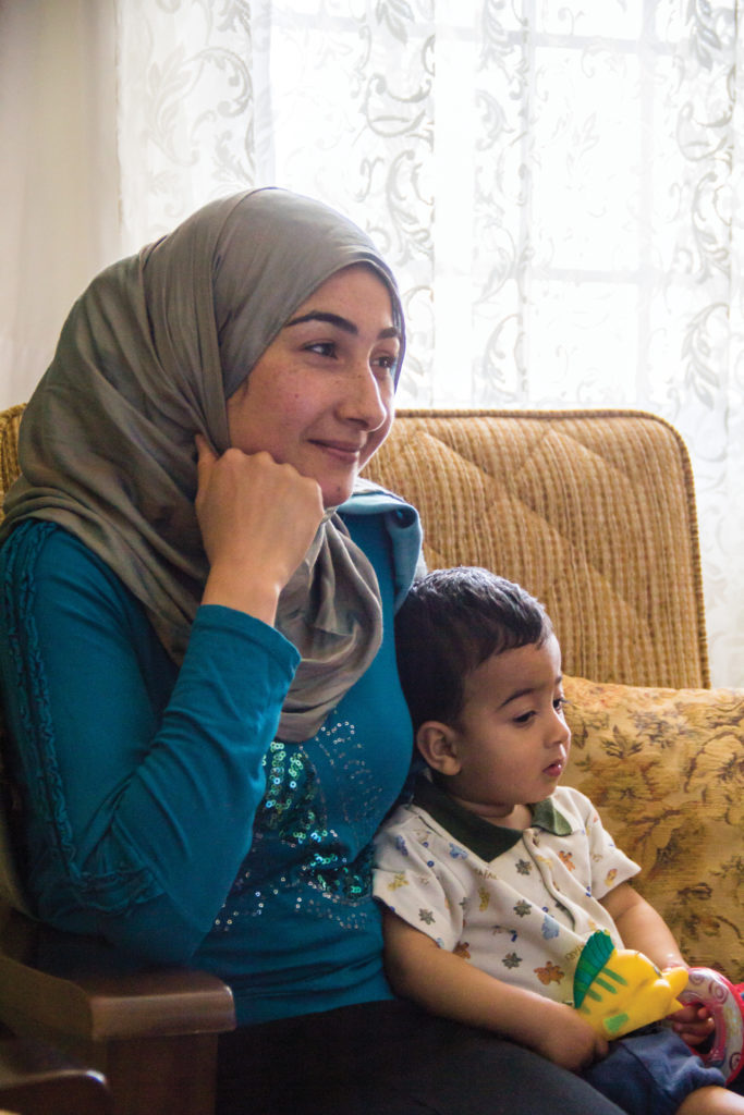 [Iona Brannon | Banner] A Syrian refugee in Turkey tells her story while holding her young son.